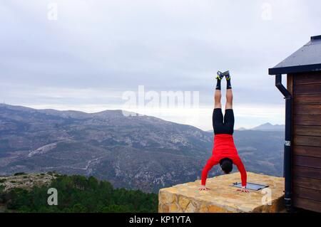 Sportswoman doing handstands in the mountains of Quatretondeta, Alicante, Valencia, Spain - Stock Photo