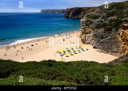Atlantic Ocean shore, Beliche beach, Praia do Beliche near Sagres, in background hidden in fog monumental cliff - Stock Photo