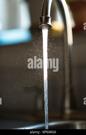 Closeup of water droplets from liquid stream of kitchen faucet, isolated by blured background - Stock Photo