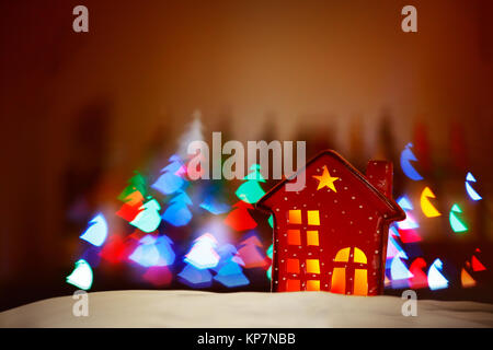 Beautiful Christmas decor, tiny red decorative house over glowing lights background, festive colorful lights in - Stock Photo