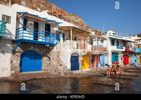 Tourists in front of the fisherman houses with boat shelters in Klima village, Milos, Cyclades Islands, Greek Islands, - Stock Photo