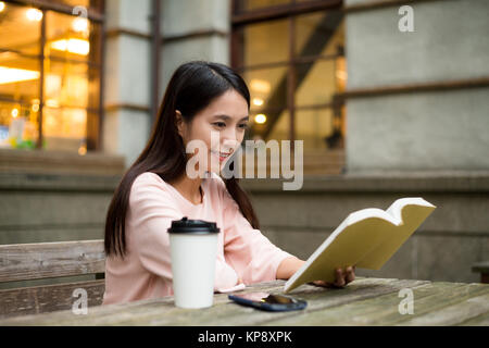Woman reading book at outdoor cafe - Stock Photo