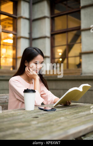 Young Woman reading book with coffee - Stock Photo