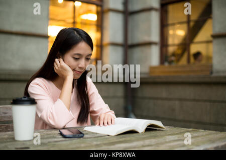 Young Woman reading on book - Stock Photo