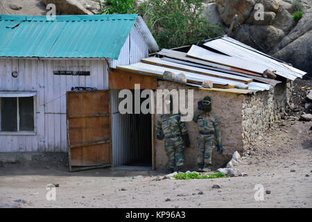 Two dummies dressed in camouflage uniforms soldiers stand near the wall of a small village house. - Stock Photo