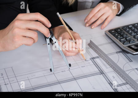 Architects Working On Blueprint At Desk In Office - Stock Photo