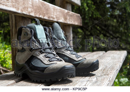 Grey hiking shoes on a bench - Stock Photo