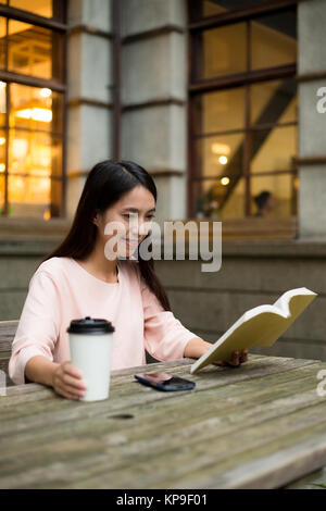 Woman reading book at outdoor restaurant - Stock Photo