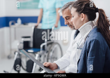 Doctor examining x-ray and medical records of an injured young patient with cervical collar and nurse pushing a - Stock Photo