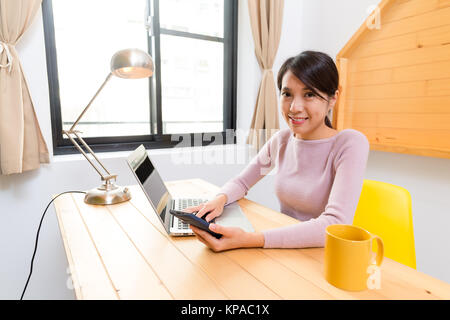 Young woman use of the mobile phone with laptop computer - Stock Photo