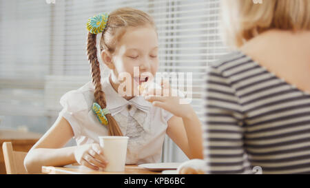 Girl with pigtails eats cakes with her mum in the cafe - Stock Photo