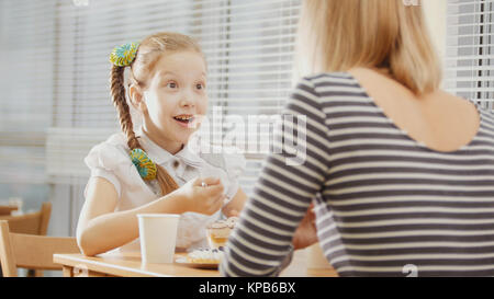 Girl with pigtail with her mum in the cafe - teen feels surprised - Stock Photo