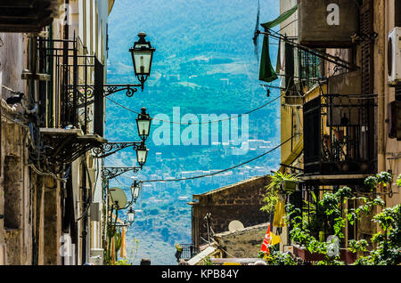Steep street with lampposts and old constructions with their balconies in the city of monreale near palermo sicily - Stock Photo