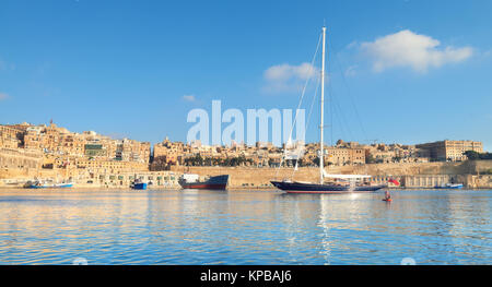 Sailing ship enters Grand Valetta bay with a view over Valetta's traditional architecture on a bright day. Panoramic - Stock Photo
