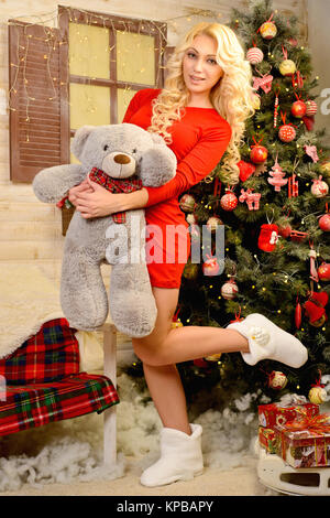 Merry girl in red dress standing next to a Christmas tree hugging a teddy bear. Volgograd region, Russia, November - Stock Photo