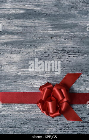 a red satin ribbon gift bow on a rustic gray wooden surface, with a blank space - Stock Photo