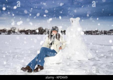Brunette Caucasian woman with snow sculpture - Stock Photo
