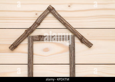 small house made of branches on wood background - Stock Photo
