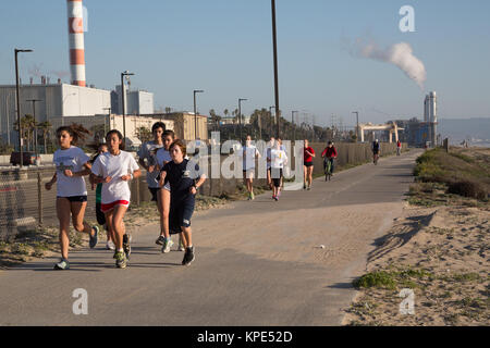 High school track team running past a power plant at Dockweiler State Beach, Los Angeles, CA - Stock Photo