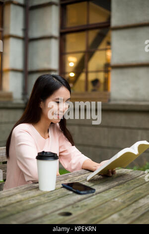 Asian Woman reading book at outdoor cafe - Stock Photo