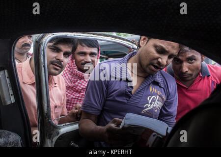 Uttar Pradesh, India. Group of men consult a guidebook - Stock Photo