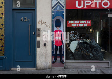 The squashed perspective of a grenadier guardsman standing as sentry next to a doorway and a closed down business - Stock Photo