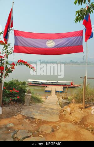 Laos flag separating the border between Thailand, Vietnam and Myanmar at the Golden Triangle, with pathway leading - Stock Photo
