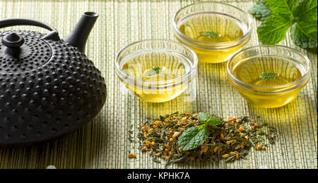 Japanese Fresh Organic Green Tea and tea leaves with clear drinking glasses and metal teapot sitting on bamboo mat - Stock Photo