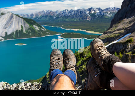 Close-up of a couple's hiking boots over a cliff overlooking a colourful alpine lake and mountain range in the distance - Stock Photo
