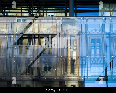Facade of a building viewed through panels of glass with reflections of yellow and blue; Belgrade, Vojvodina, Serbia - Stock Photo