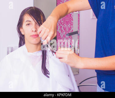 Woman with long dark wet hair having bangs haircut in hair salon by a stylist using scissors. The woman is covered - Stock Photo
