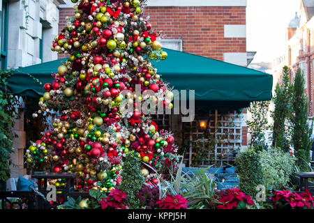 LONDON, UNITED KINGDOM - DECEMBER 12th, 2017: Christmas tree is placed outside the Ivy Market Grill restaurant in - Stock Photo