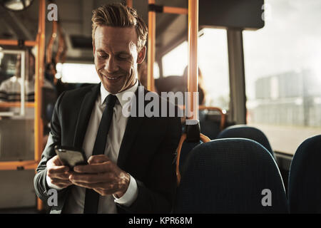 Smiling young businessman wearing a suit standing on a bus during his morning commute reading text messages - Stock Photo