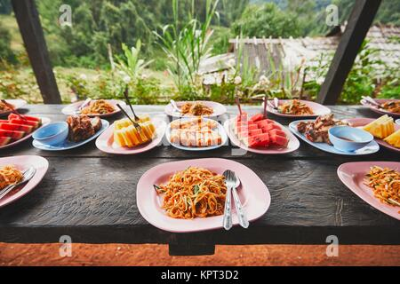 Lunch in the middle of the jungle. The table full of foods and fruits. Traditioal Pad Thai, spring rolls, melon - Stock Photo