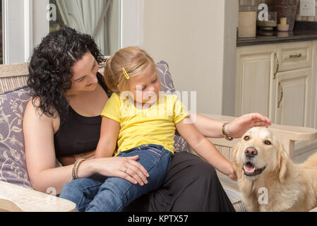 Mother and Daughter with Golden Retriever on Porch - Stock Photo