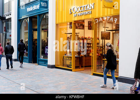 Shoppers during the daytime walking past a L'Occitane chocolate shop in Bond Street Chelmsford - Stock Photo