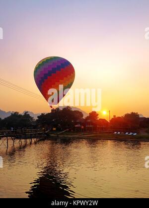 Recreation. Hot air balloon flying over the river Nam Song at sunrise. Vang Vieng, Laos. - Stock Photo