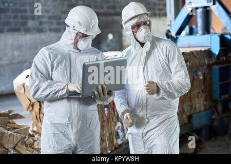 Workers in Hazmat Suits at Modern Recycling Factory - Stock Photo