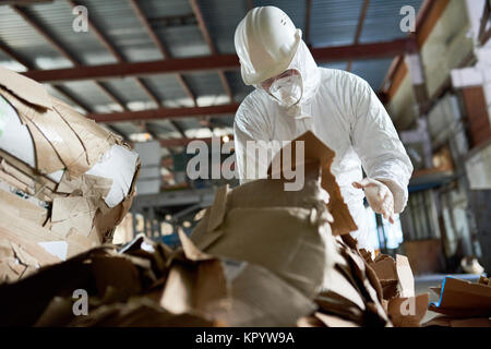 Worker in Protective Suit Sorting Cardboard - Stock Photo