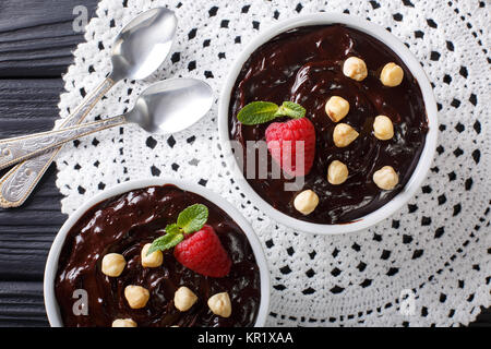 Delicious chocolate pudding with hazelnuts and raspberries close-up in a bowl on the table. horizontal top view - Stock Photo