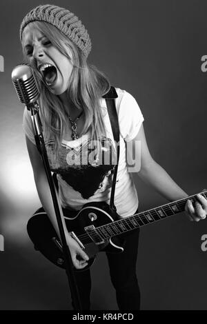 Black and white photo of a blond female screaming into an old microphone and playing electric guitar.  High contrast - Stock Photo