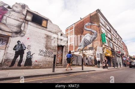 London, England, UK - July 4, 2010: Graffiti murals painted on derelict houses and office buildings in Hanbury Street - Stock Photo