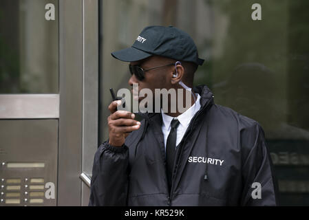 Security Guard Talking On Walkie-Talkie - Stock Photo