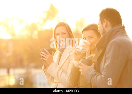 Three funny friends talking outdoors and drinking coffee at sunset - Stock Photo