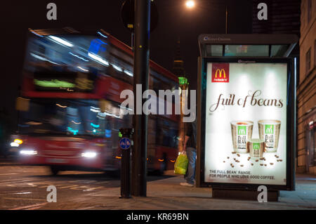 London, England, UK - October 11, 2010: A traditional red double-decker London bus pulls away from a bus stop on - Stock Photo