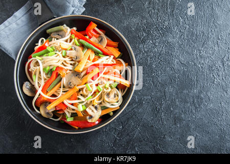 Stir fry with udon noodles, mushrooms and vegetables. Asian vegan vegetarian food, meal, stir fry over black background, - Stock Photo