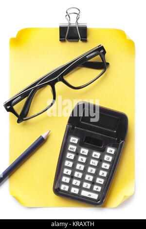 black calculator with eye glasses pencils clip yellow paper - Stock Photo