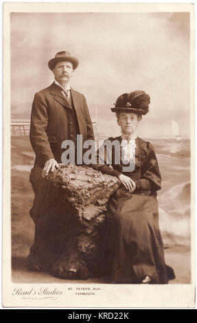 An elderly Edwardian couple pose for their photograph in the studio, with a large lump of rock to lean on, and a - Stock Photo