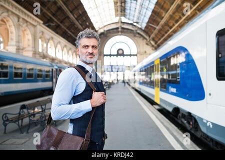 Mature businessman on a train station. - Stock Photo