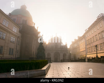 Prague on a sunrise, town square with Church of St. Francis of Assisi in morning mist - Stock Photo